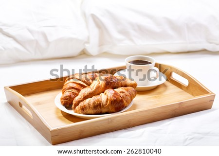 breakfast in bed with coffee and croissants - stock photo