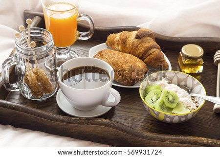Breakfast in bed with coffee, granola and yogurt, orange juice and croissants in wooden tray