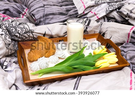 Breakfast in bed with milk, croissant and tulips