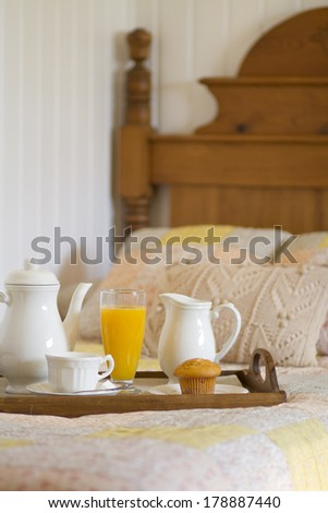 Breakfast in bed with orange juice and muffin on a tray in a country style environment - stock photo
