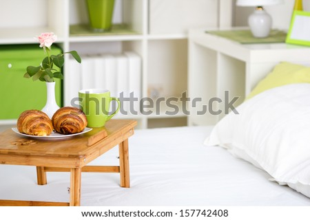 breakfast in bed with pastries on a tray  and a rose in the vase - stock photo