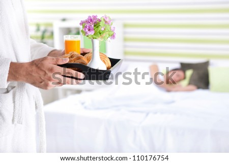 Breakfast in bed, young man bringing breakfast in bed with his girlfriend - stock photo