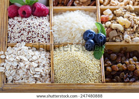 Breakfast items in wooden box with grains and berries - stock photo