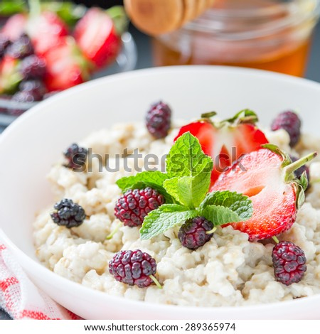 Breakfast - oatmeal, berries, mint, honey, dark background