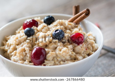 Breakfast oatmeal porridge with cinnamon, cranberries and blueberries, front view, selective focus, close up - stock photo