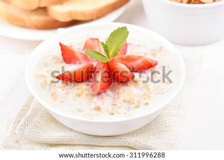 Breakfast oatmeal porridge with strawberry slices  - stock photo