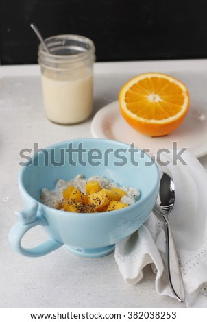 Breakfast; oatmeal with fresh mango topping in a blue cup with a bird on the handle. Fresh navel and blood orange slices on a white plate.C