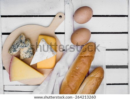 Breakfast of cheese, bread and eggs on a light wooden background - stock photo