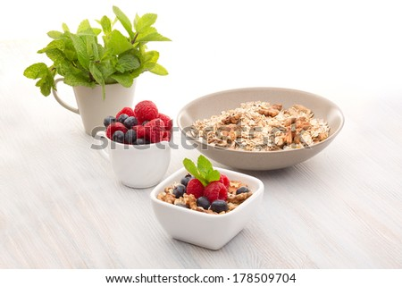 Breakfast of muesli, berries and peppermint - stock photo