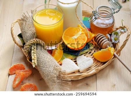 breakfast of oranges, orange juice, milk, honey and bread - stock photo
