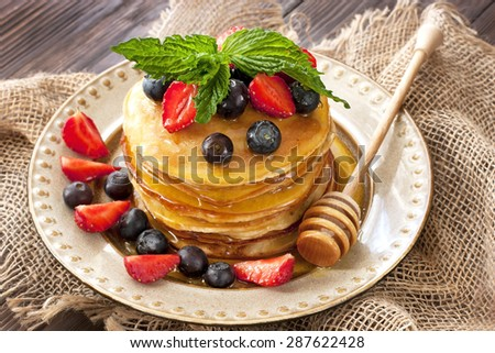 Breakfast of pancakes on  ceramic plate. Pancakes drenched with honey - stock photo