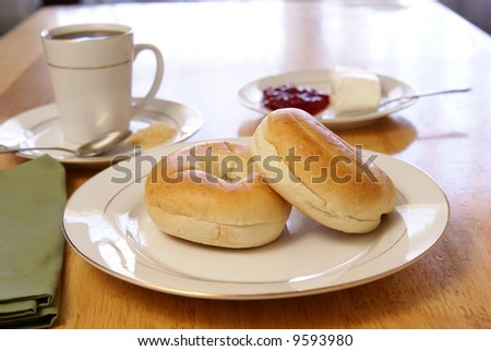 Breakfast of plain bagels with coffee, cream cheese, and strawberry preserves. - stock photo