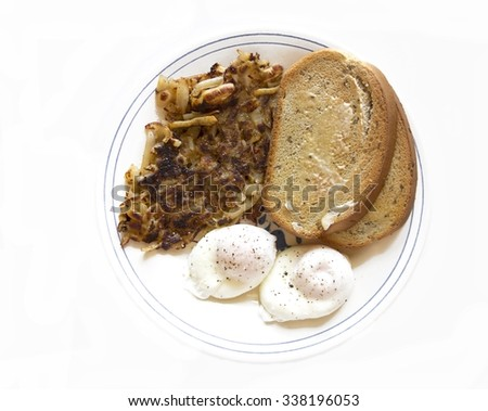Breakfast of poached eggs, hash browns and rye toast.
