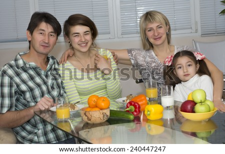 Breakfast of poly ethnic family.  Family of four people has breakfast. People of different nations - Caucasian and Asian, healthy food - fruits, colorful vegetables, juice and milk, modern lifestyle.