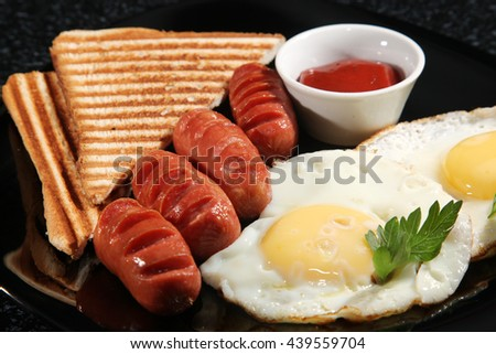 breakfast of scrambled eggs with sausage on black plate - stock photo