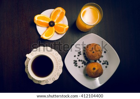 Breakfast on dark wood surface including coffee, muffins, orange juice and slices of oranges placed upon small white plate - stock photo