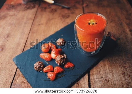 Breakfast on the working table; strawberry orange lemon and passion fruit smoothie. Served with fresh strawberries and chocolate on a stone slate. SOFT focus on the smoothie glass. - stock photo