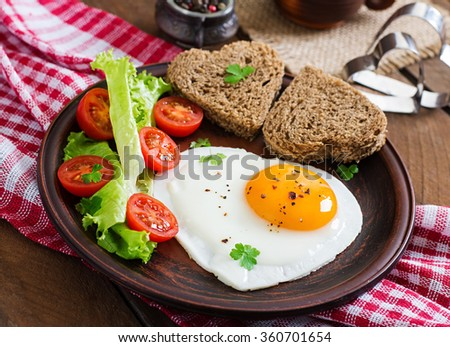 Breakfast on Valentine's Day - fried eggs and bread in the shape of a heart and fresh vegetables.  - stock photo
