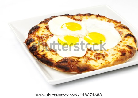 Breakfast pizza dish with ham sausage and bacon topped with three eggs - stock photo
