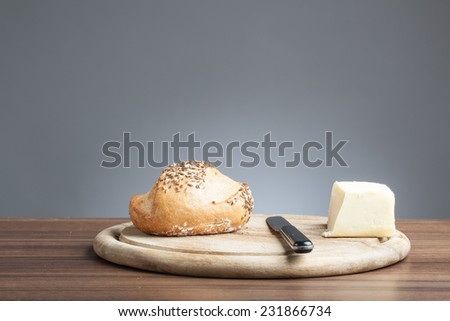 Breakfast plate with knife, wholemeal bread roll with carawy seeds and a piece of butter. - stock photo
