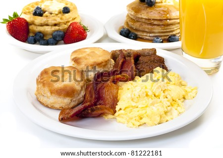 Breakfast plate with scrambled eggs, bacon, and buttermilk biscuits.  Waffles, pancakes, and orange juice in background.  Isolated on white background. - stock photo