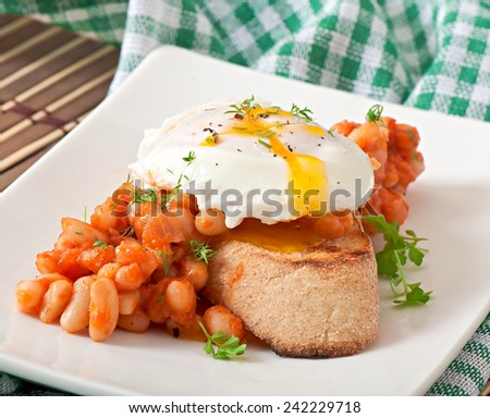 Breakfast - poached egg with toast, baked beans with tomato sauce - stock photo