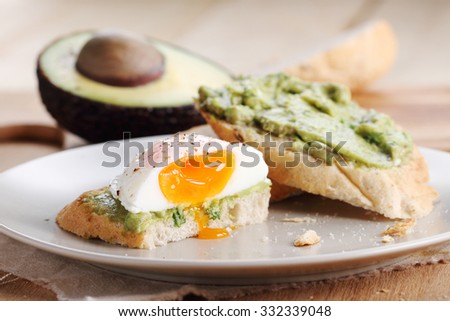 Breakfast, poached eggs with avocado salad on toast - stock photo