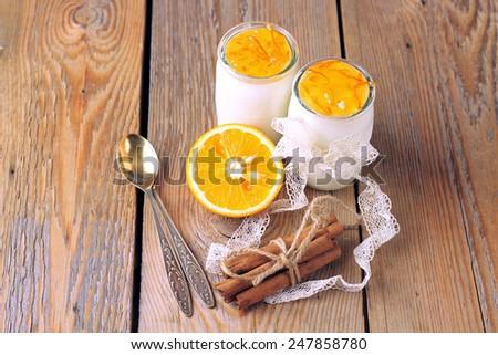 Breakfast products (homemade yogurt, orange and cinnamon jam) on a wooden table. Selective focus - stock photo