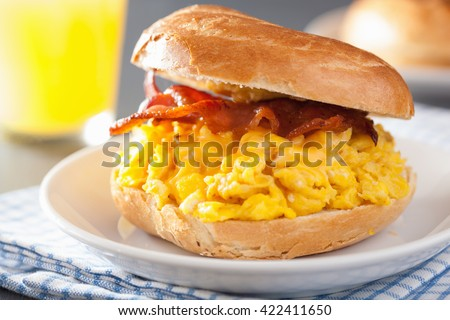 breakfast sandwich on bagel with egg bacon cheese - stock photo