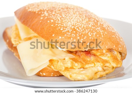 Breakfast Sandwich with Bacon and Fried Scrambled Egg. Close Up of Toast with Hot Cheese and Poached Ham. Toasted English Fried Burger on White Background. Flat Bread Loaf Bagel, Studio Isolated. - stock photo