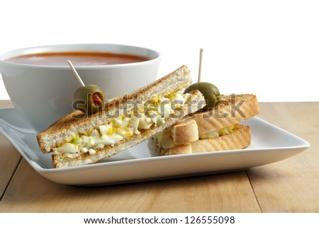 Breakfast sandwich with egg and olive fruits on stick, and tomato soup on white bowl - stock photo
