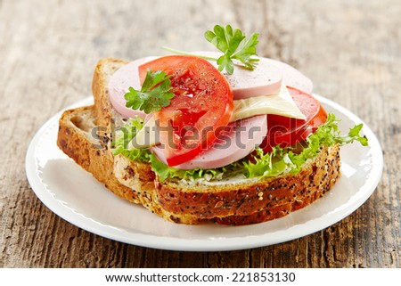 breakfast sandwich with sliced sausage and tomato on wooden table - stock photo