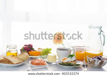 Breakfast served in front of the window with porridge, poached egg, salmon, berries, fruits ans orange juice - stock photo