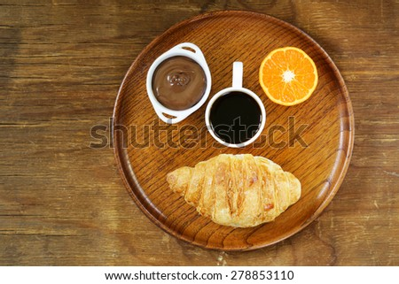 breakfast serving funny face on the plate (croissant, chocolate spread, orange and coffee) - stock photo