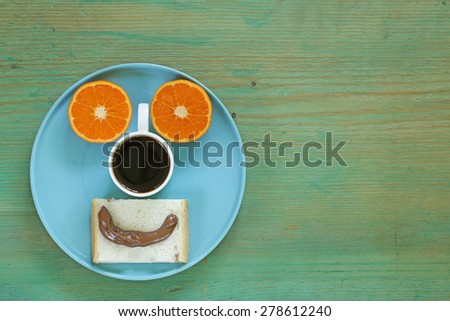 breakfast serving funny face on the plate (toast, chocolate spread and orange) - stock photo