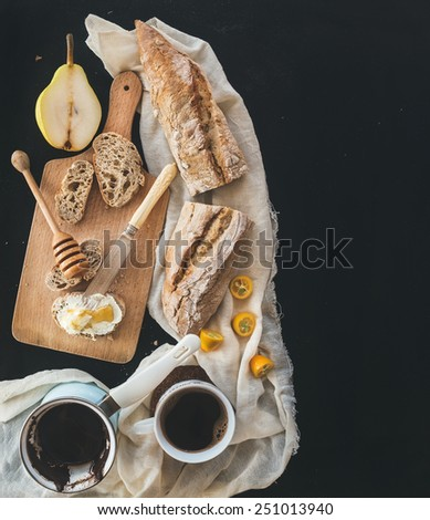 Breakfast set: a pot of coffee, a cup on a kitchen towel, kumquats, pears, baguette slices with butter cream and honey on a rustic wooden board over a black backdrop with a copy space. Top view - stock photo