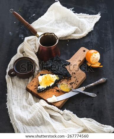 Breakfast set. Black bread toasts with tangerine marmelade and mascarpone cheese, fresh coffee on dark grunge table surface - stock photo
