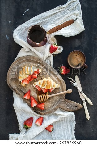 Breakfast set. Freshly baked croissants with strawberries, mascarpone, honey and coffee on rustic wooden board over dark grunge backdrop, top view - stock photo