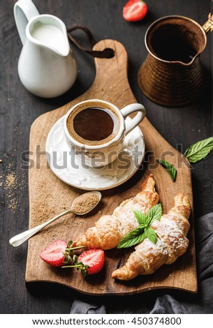 Breakfast set. Freshly baked croissants with strawberry, mint leaves and cup of coffee on wooden board served with pitcher and copper coffee pot over dark wooden backdrop, top view, selective focus - stock photo