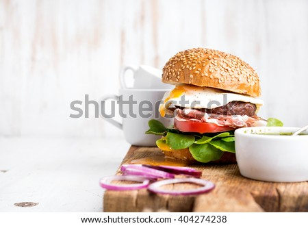 Breakfast set. Homemade beef burger with fried egg and vegetables, onion rings and coffee cups on wooden board, white painted background. Selective focus, copy space - stock photo