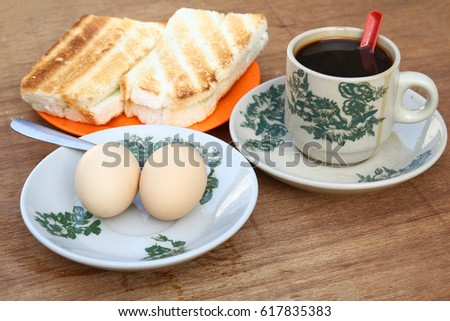 Breakfast set of coffee, half boiled eggs and toast, a popular meal in Malaysian and Singaporean coffeeshops.
