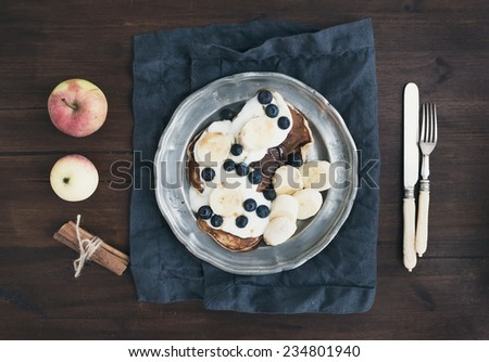 Breakfast set on dark wooden desk: apple and cinnamon pancakes with yogurt, banana, blueberry and maple syrup in a rustic metal plate. Top view - stock photo