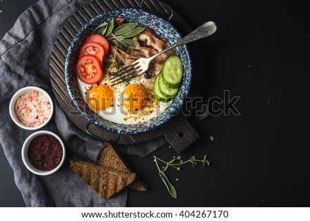 Breakfast set. Pan of fried eggs with bacon, fresh tomato, cucumber, sage and bread on dark serving board over black background, top view, copy space - stock photo