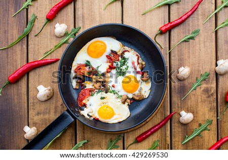 Breakfast set. Pan of fried eggs with mushrooms, fresh tomato, on rustic serving board over wooden background - stock photo