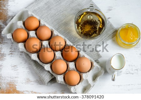 Breakfast setting - eggs in a cardboard tray, milk in a jug, green tea and honey, view from above