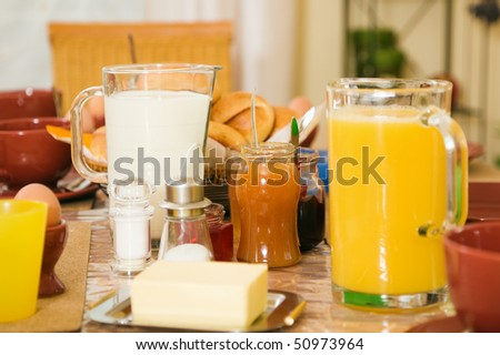 Breakfast still life with orange juice, focus on marmalade jar