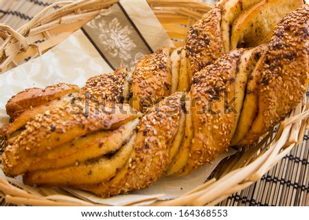 Breakfast still life with twisted bread with garlic and sesame seeds in a wicker basket