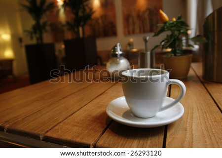 Breakfast table near to the window with a cup of coffe - stock photo