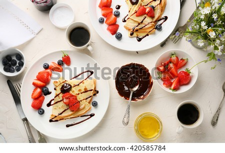 breakfast table set with crepes, food top view - stock photo