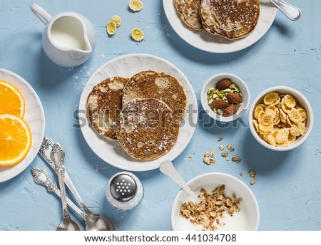 Breakfast table. Whole wheat pancakes, greek yogurt with homemade granola, orange slices, nuts, corn flakes, on a blue stone background - stock photo